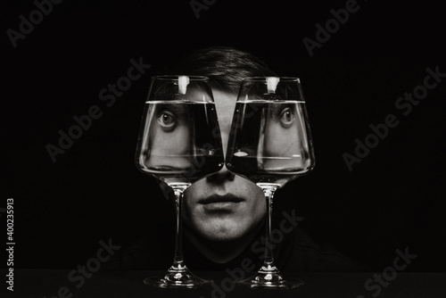 portrait of a strange man looking through two glasses of water Fotobehang