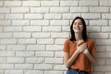What A Relief. Happy Young Woman Posing Close To Wall Of Bricks With Closed Eyes Feeling Grateful Hopeful. Millennial Female Putting Hands On Chest Over Heart Express Sincere Feelings. Copy Space
