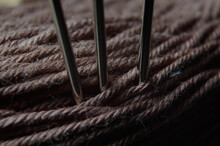 Three Sewing Needles Are Inserted Into A Spool Of Thread. Close-up.
