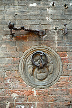 Close-up Of An Old Brick Wall With An Iron Ring For Tying Horses And A Torch Holder, Antique Details In Wrought Iron, Siena, Tuscany, Italy
