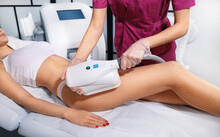Young Woman Getting Cryolipolyse Treatment In Cosmetic Cabinet. Fat Freezing Technology On Legs. Cool Sculpting Procedure