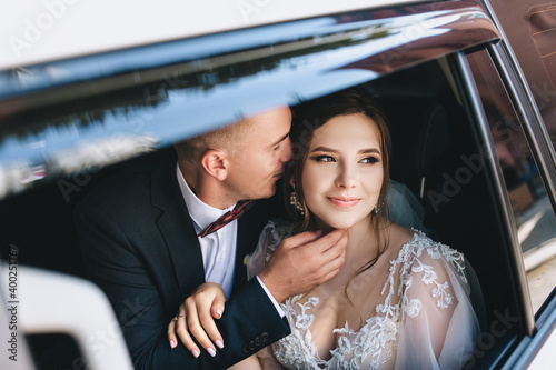 Fotomural A beautiful bride with a bouquet of flowers in a lace dress and a groom in a blue suit are sitting and hugging inside a white car