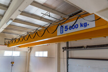 Yellow Colored Heavy Load Handling Crane Mounted On The Ceiling Ready To Use In The Closed Warehouse Area