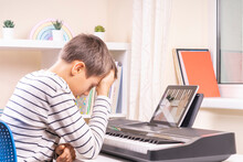 Sad Frustrated Boy Has Difficulty Learning To Play Piano At Home. Kid Using Digital Tablet To Watch Video Lesson. Online Learning Difficulties