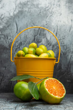 Vertical View Of A Yellow Bucket Full Of Fresh Green Tangerines And Cut In Half Tangerines On Gray Background