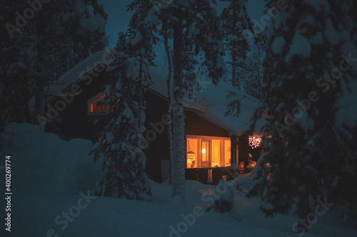 Tela A night view of cozy wooden scandinavian cabin cottage chalet house covered in s