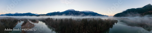Aerial Panoramic Canadian Nature Landscape with mountains in background. Sunny Sunrise Sky. Taken in Squamish, North of Vancouver, British Columbia, Canada.