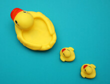 Rubber Toy Ducks On Teal Background, Flat Lay