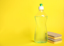 Cleaning Product And Sponges On Yellow Background, Space For Text. Dish Washing Supplies