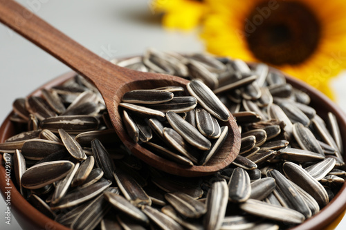Fototapeta Raw sunflower seeds and wooden spoon in bowl, closeup obraz