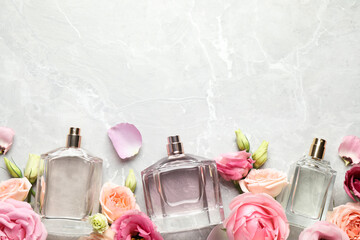Flat lay composition of different perfume bottles and flowers on light grey marble background, space for text