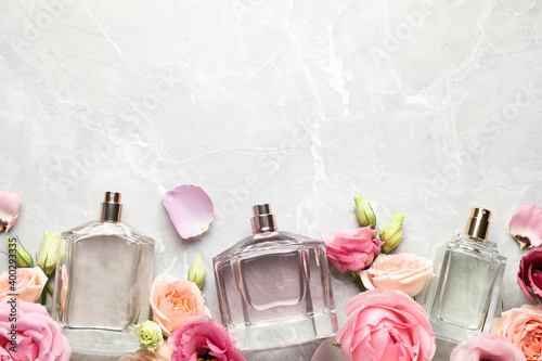 Fototapeta Flat lay composition of different perfume bottles and flowers on light grey marble background, space for text obraz