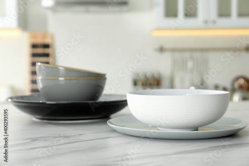 Billede på lærred Set of ceramic tableware on white marble table in kitchen