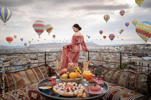 Obraz Happy women on rooftop of cave house enjoying of Goreme city panorama, Cappadocia Turkey. 3D balloons in the sky. - fototapety do salonu