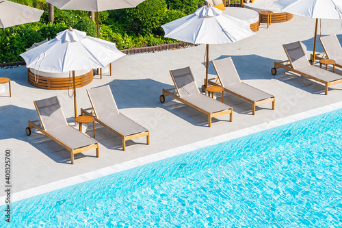 Photo Umbrella and deck chair around outdoor swimming pool in hotel resort