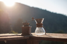 Hot Arabica Coffee And Vintage Coffee Drip Equipment On Wooden Table In The Morning With Mountain And Nature Background