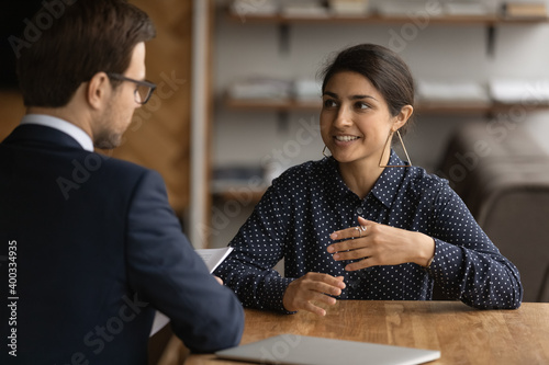 Confident young Indian woman have recruitment talk with male employer at office interview. Ethnic female job candidate speak with boss or recruiter at meeting. Employment, hiring concept.
