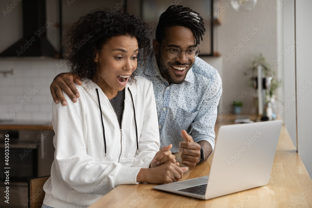 Fototapeta Amazed young biracial couple look at laptop screen shocked by unexpected online sale offer or discount. Stunned millennial African American man and woman surprised by amazing good message on computer.