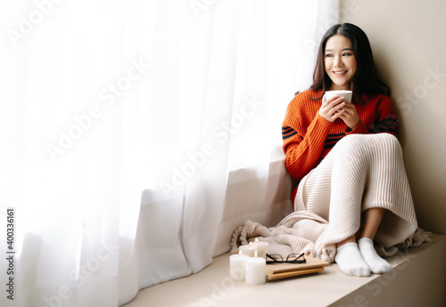 Fotografie, Obraz Young beautiful happy Asian woman wearing knitted warm sweater sitting home in the chair by the window with cup of hot drink at home