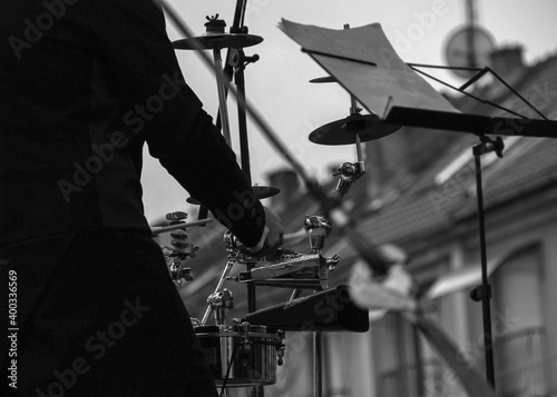 Obraz na plátne View from behind of a percussionist performing on an outdoor stage (B/W)