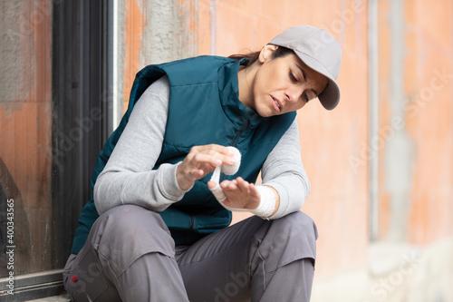 Fotografering female worker bandaging her hand after incident