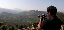 A Tourist Photographing The Western Ghat Mountain Ranges In Iravikulam National Park.