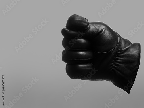 Fototapeta black leather glove shows fig sign left gesture. isolated neutral background. copy space obraz