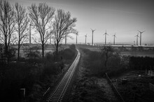 Railroad Tracks Lead To The Horizon Where Some  Wind Turbines Stand