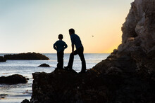 Father And Son Silhouette Standing Together On Rock Ledge Looking Out At The Sunset On The Ocean Horizon. Loving Relationship Between Dad And His Child