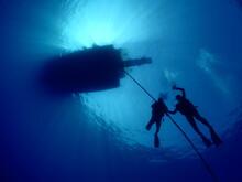 Scuba Divers Ascending Descending On The Line Of Boat Rope Underwater Blue