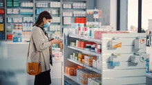 Pharmacy Drugstore: Portrait Of Beautiful Young Woman Wears Protective Face Mask, Searches To Buy Best Medicine, Drugs, Vitamins. Shelves Full Of Health Care, Welness, Cosmetics, Beauty Products