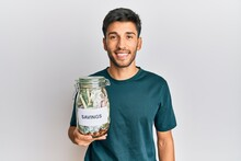 Young Handsome Man Holding Jar With Savings Looking Positive And Happy Standing And Smiling With A Confident Smile Showing Teeth