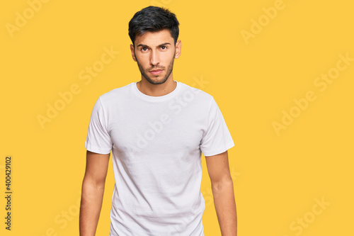 Fototapeta Young handsome man wearing casual white tshirt skeptic and nervous, frowning upset because of problem