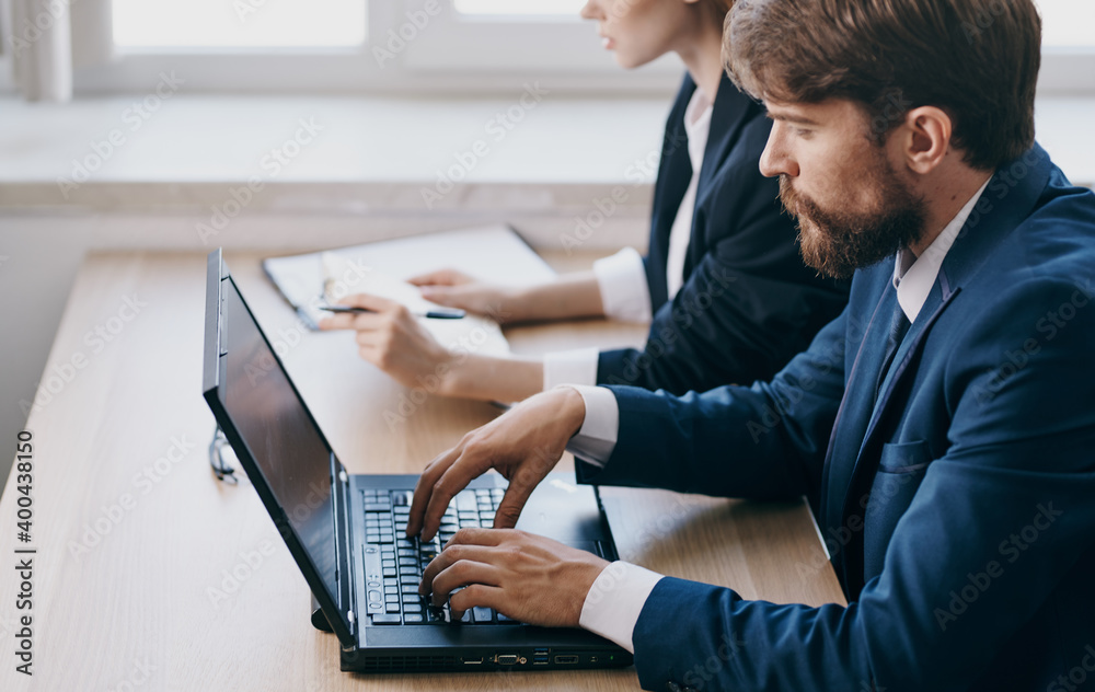 Fototapeta Work colleagues in suits working desk laptop office managers team
