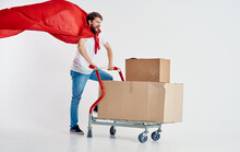 Courier With Cardboard Boxes In Cargo Trolley And Red Superhero Cloak