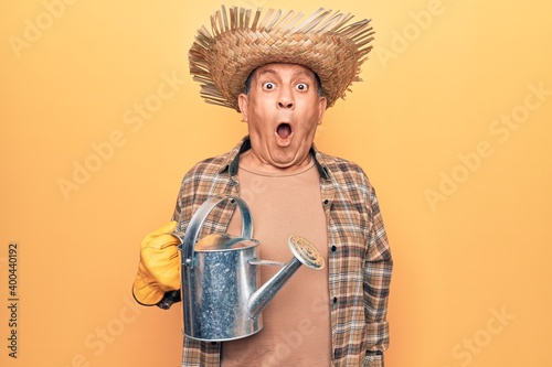 Fotografija Senior man with grey hair wearing gardener hat holding watering can scared and a