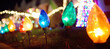 Close-up photo of Christmas and New Year decorations. Fence decorated with a multicolored garland. Outdoor Xmas decorations