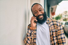 Handsome Modern African American Man With Beard Speaking On The Phone At The City With A Happy Smile