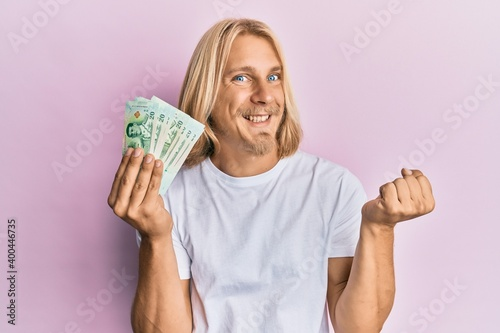 Canvas-taulu Caucasian young man with long hair holding 20 thai baht banknotes screaming prou
