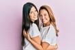 Leinwandbild Motiv Beautiful hispanic mother and daughter smiling happy hugging over isolated pink background.
