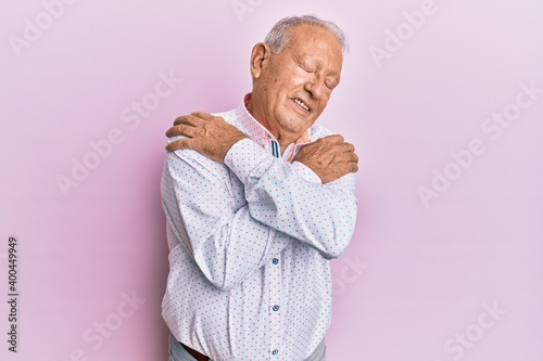Senior caucasian man wearing casual clothes hugging oneself happy and positive, smiling confident Wallpaper Mural