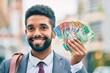 Leinwandbild Motiv Young african american businessman smiling happy australian dollars banknotes at the city.