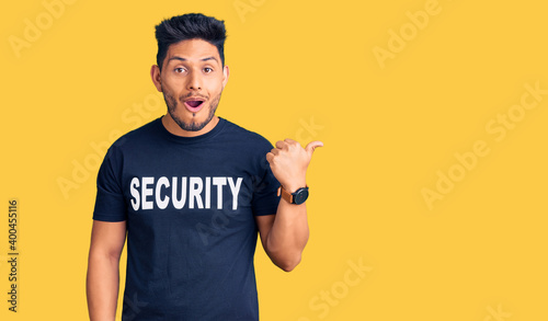 Photographie Handsome latin american young man wearing security t shirt surprised pointing with finger to the side, open mouth amazed expression