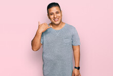 Young Latin Man Wearing Casual Clothes Smiling Doing Phone Gesture With Hand And Fingers Like Talking On The Telephone. Communicating Concepts.