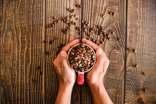 Hands Holding A Mug Full Of Roasted Coffee Beans And With A Wooden Backdrop Can Be Used As A Background