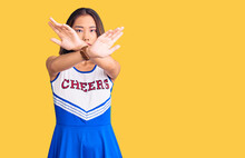 Young Beautiful Chinese Girl Wearing Cheerleader Uniform Rejection Expression Crossing Arms And Palms Doing Negative Sign, Angry Face