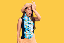 Young Beautiful Latin Girl Wearing Hawaiian Lei And Summer Hat Surprised With Hand On Head For Mistake, Remember Error. Forgot, Bad Memory Concept.