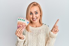 Beautiful Caucasian Blonde Woman Holding 10 Euro Banknotes Smiling Happy Pointing With Hand And Finger To The Side