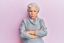 Senior Grey-haired Woman Wearing Wool Sweater And Winter Hat Skeptic And Nervous, Disapproving Expression On Face With Crossed Arms. Negative Person.