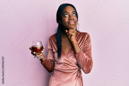 Young african american woman wearing sexy party dress holding cocktail serious face thinking about question with hand on chin, thoughtful about confusing idea